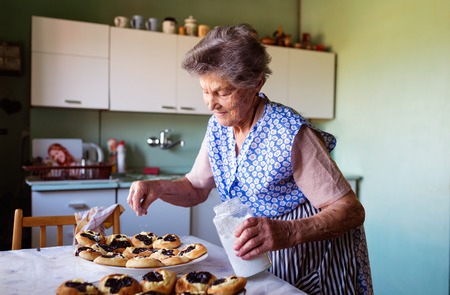 woman baking: Senior woman baking pies in her home kitchen. Sprinkling freshly baked buns with powdered sugar. Stock Photo