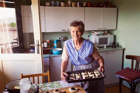年配の女性は彼女の家の台所でパイを焼きます。 カッテージ チーズとジャム付きパンを充填します。