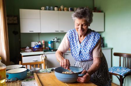 Evine mutfakta Senior woman pişirme turta. Bileşenlerin karıştırılması.