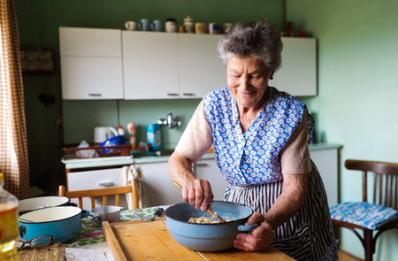 Starší žena pečení koláče v její domácí kuchyně. Míchání složek.