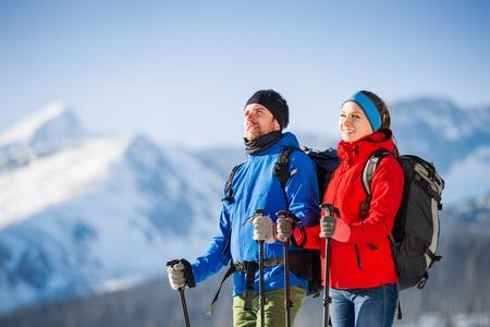 sportsman: Par de caminata joven afuera en las montañas soleados de invierno