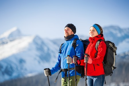 Young couple hiking outside in sunny winter mountains Stock Photo