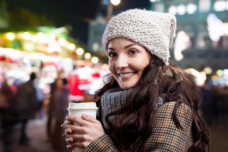 anochecer: Mujer joven hermosa con la taza de café en la ciudad