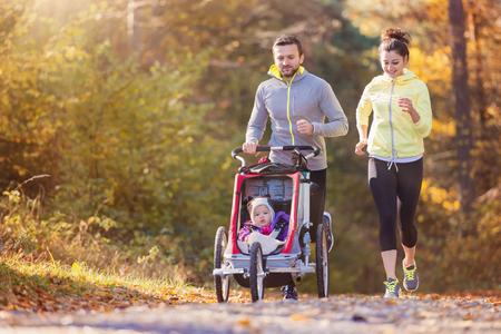 Família nova bonita com o bebê no carrinho de corrida correr fora na natureza do outono
