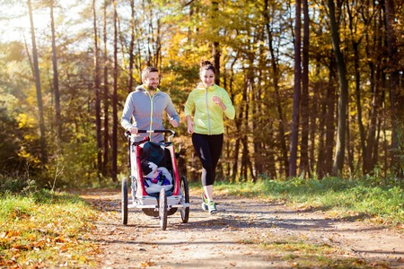 autumn in the park: Beautiful young family with baby in jogging stroller running outside in autumn nature