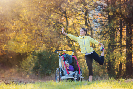 Beautiful young mother with her daughter in jogging stroller running outside in autumn nature Stock Photo