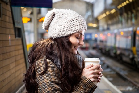 tube station: Beautiful young woman with coffee cup in the city