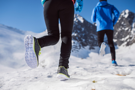 black guy: Legs of two runners outside in winter nature Stock Photo