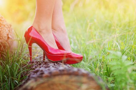 tacones rojos: mujer joven irreconocible con tacones rojos de pie sobre un tronco Foto de archivo