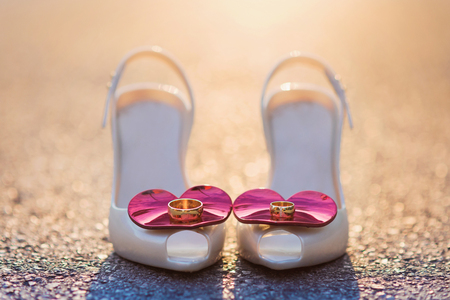 laid: Bridal shoes and wedding rings laid on the ground