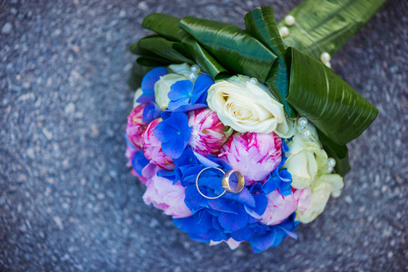 laid: Wedding bouquet and rings laid on the ground