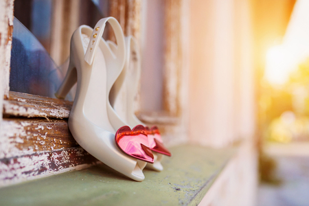 high heel shoes: Bridal shoes with red hearts laid on window parapet