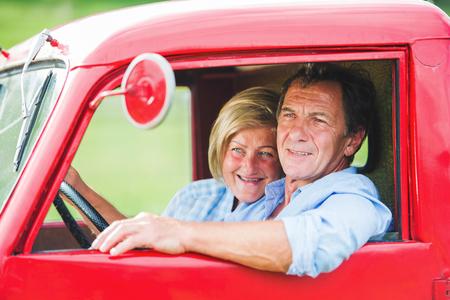 vintage car: Senior couple in their vintage red car