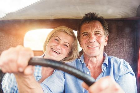 Ältere Paare, die in ihrem Jahrgang roten Auto Standard-Bild