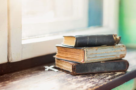 old windows: Stack of old books laid on windowsill Stock Photo