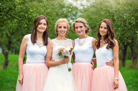 Beautiful young bride with her bridesmaids outside in nature Stock Photo