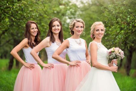 Mooie jonge bruid met haar bruidsmeisjes buiten in de natuur