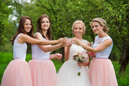 bridesmaids: Beautiful young bride with her bridesmaids outside in nature Stock Photo