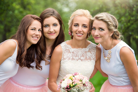 organza: Beautiful young bride with her bridesmaids outside in nature Stock Photo