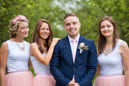 bridesmaids: Handsome young groom with her bridesmaids outside in nature