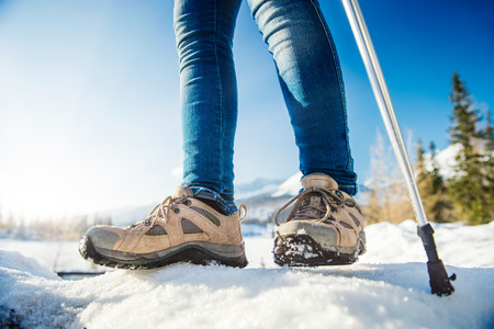 range of motion: Unrecognizable woman hiking outside in sunny winter mountains Stock Photo