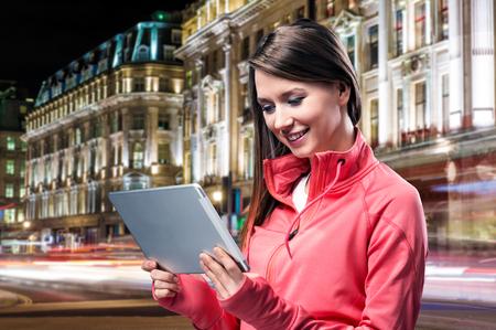 personas leyendo: Corredor joven con el teléfono inteligente en la ciudad Foto de archivo