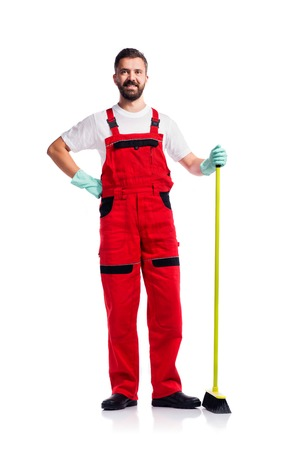 cleaner: Young handsome cleaner in red overalls. Studio shot on white background