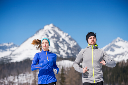 jogging: Young couple jogging outside in sunny winter mountains