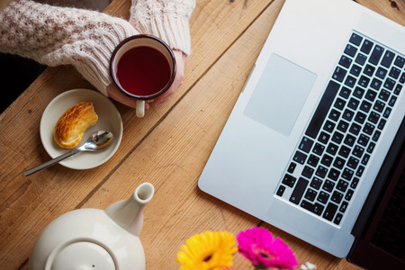 Beautiful woman relaxing at home with notebook and cup of  coffee Archivio Fotografico