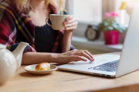 femme blonde: Belle femme de d�tente � la maison avec ordinateur portable et une tasse de caf�