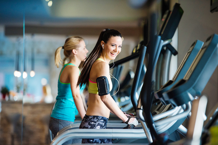 gym: Two young beautiful women working out in gym