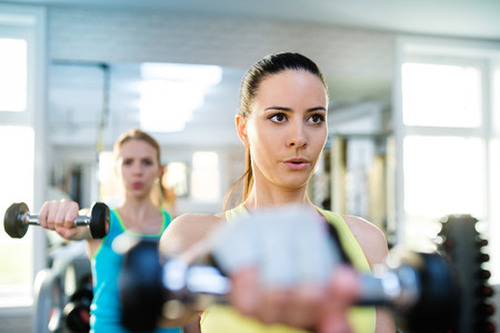 women working out: Two young beautiful women working out in gym