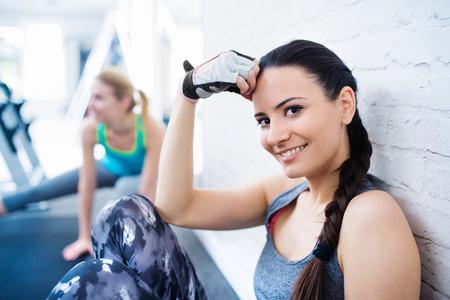 cabello rubio: Dos hermosas mujeres jóvenes que trabajan en el gimnasio
