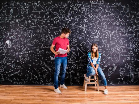 Estudiantes jóvenes hermosas en frente del gran pizarra Foto de archivo