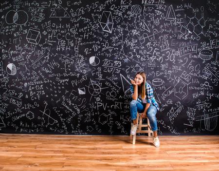 signos matematicos: Niña de la escuela joven hermosa delante de la gran pizarra Foto de archivo