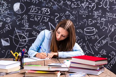 colegiala: Hermosa estudiante haciendo su tarea al frente de la gran pizarra