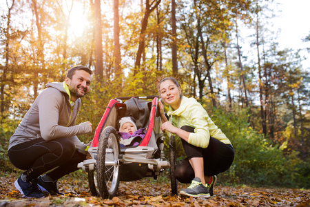 family with baby: Beautiful young family with baby in jogging stroller outside in autumn nature