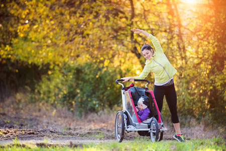 pram: Beautiful young mother with her daughter in jogging stroller running outside in autumn nature Stock Photo