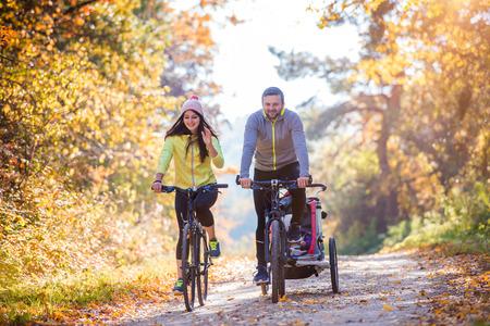 ciclismo: Familia joven hermosa con el bebé en cochecito que activa el ciclismo al aire libre en la naturaleza del otoño