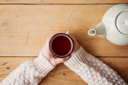 Mooie vrouw ontspannen thuis met kopje thee