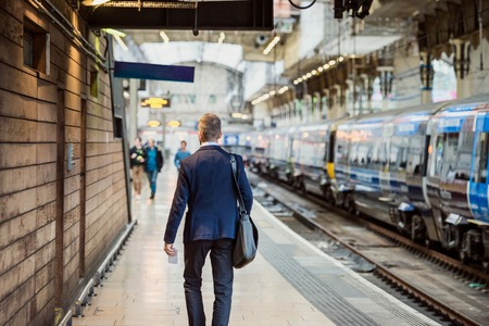 travel bag: Young handsome businessman standing at the crowded station Stock Photo