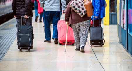 travel bag: Travellers walk through train station carrying suitcases Stock Photo
