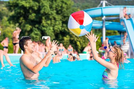 아름 다운 젊은 부부 수영장에서 외부 재미