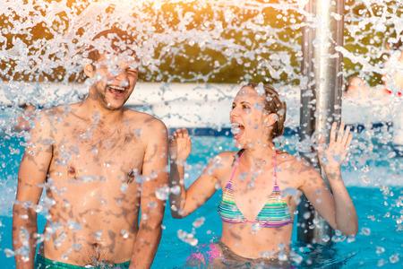 couple having fun: Beautiful young couple having fun outside in the swimming pool