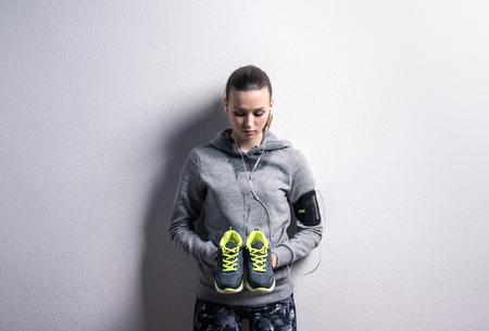 Mooie jonge sportvrouw. Studio geschoten op een grijze achtergrond.