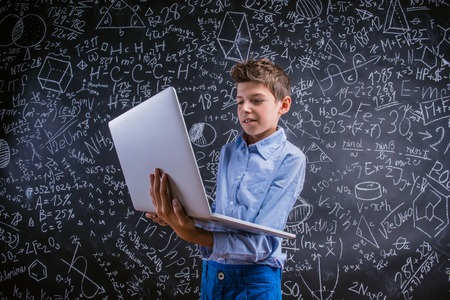 fond de texte: Jeune beau gar�on de l'�cole avec ordinateur portable, debout, devant grand tableau noir