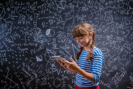 math symbols: Cute little girl with tablet in front of big blackboard Stock Photo