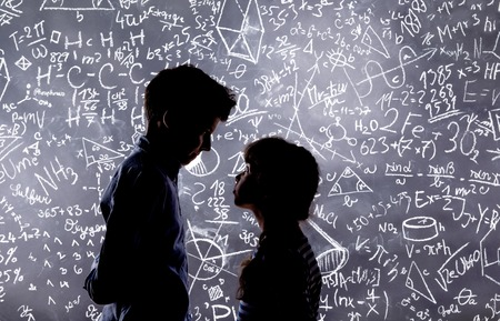 of boy and girl: Cute little boy and girl in front of a big blackboard. Studio shot on black background.