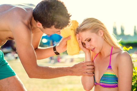 sunstroke: Young woman with heatstroke on a beach Stock Photo