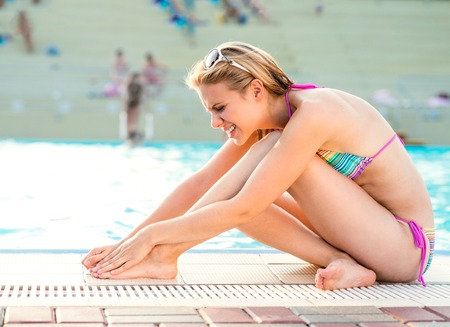 hurt: Young woman with injured leg at the swimming pool Stock Photo